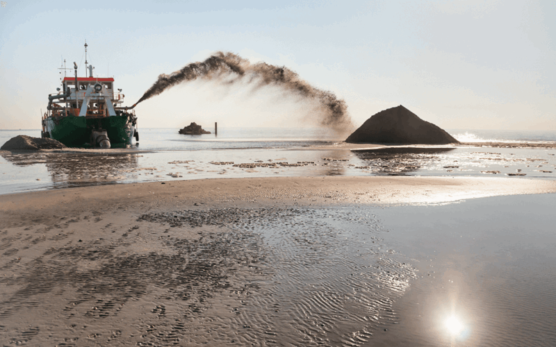 Dredging vessel spraying sand and dirt